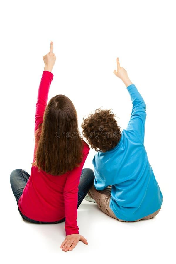 Fille et garçon s'asseyant et se dirigeant sur le fond blanc images libres de droits