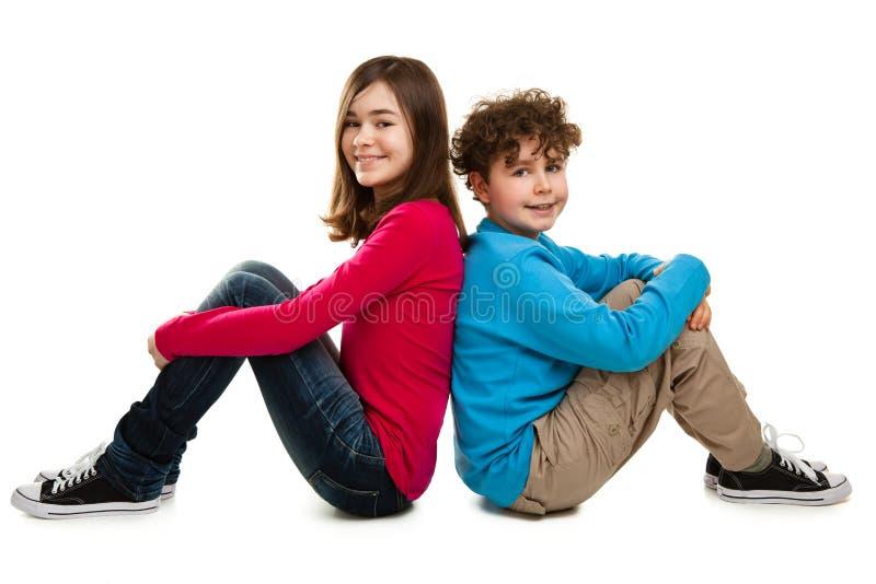 Fille et garçon s'asseyant sur le fond blanc photo stock