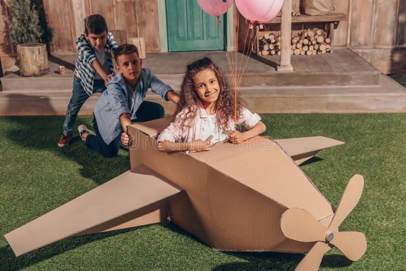 Fille et garçons jouant avec l'avion de carton ensemble photos libres de droits