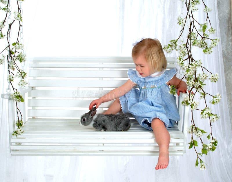 Fille et lapin sur l'oscillation photo stock