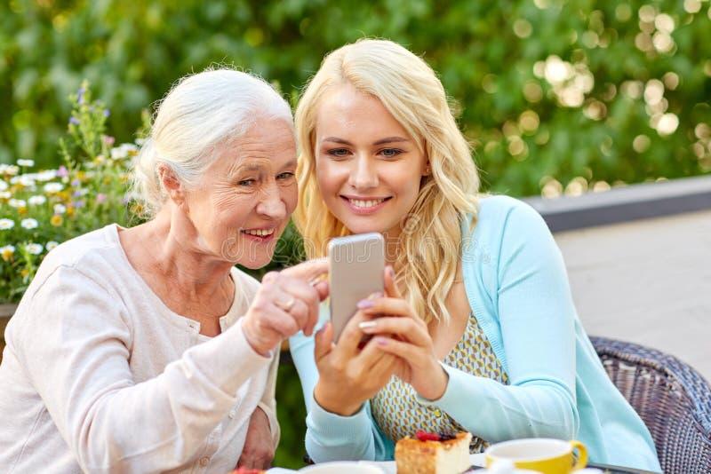 Fille et mère supérieure avec le smartphone au café images libres de droits