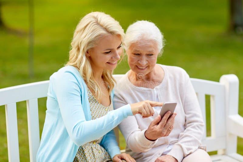 Fille et mère supérieure avec le smartphone au parc photos stock