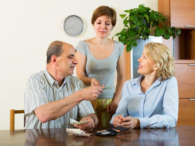 Fille et parents adultes avec l'argent photos libres de droits
