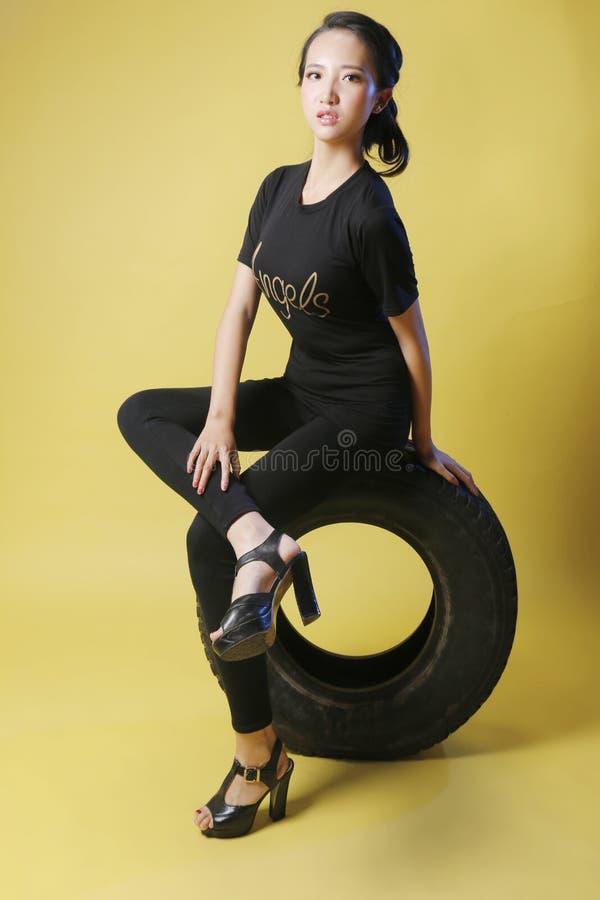 Fille et pneu asiatiques photographie stock