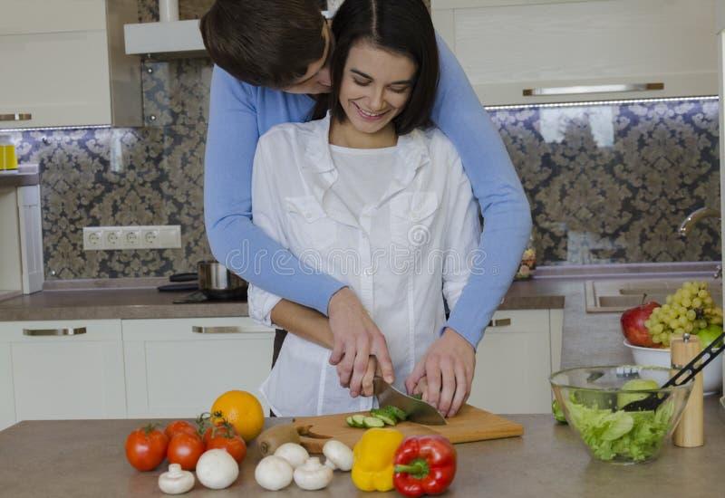 Fille et type dans la cuisine préparant la nourriture photos stock