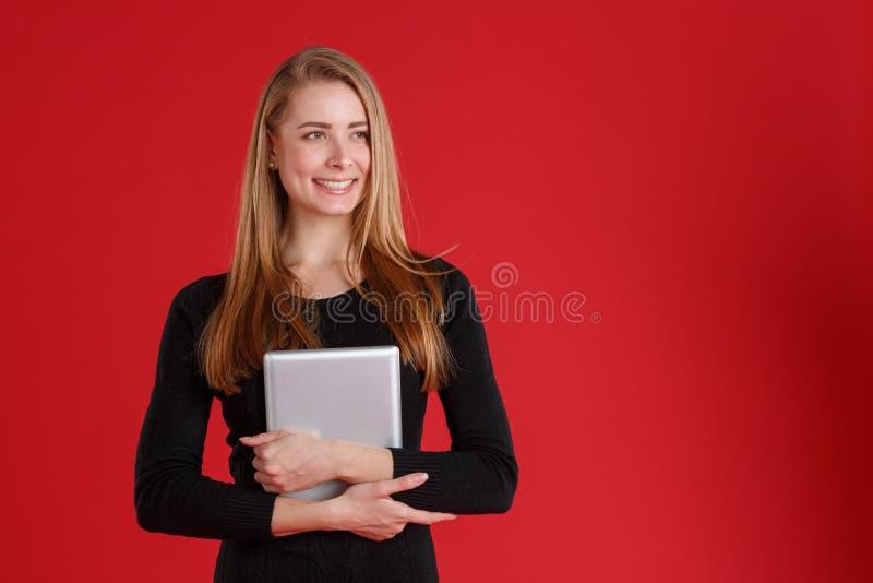 Fille européenne heureuse se tenant dans le comprimé de mains de couleur et du sourire gris Sur un fond rouge images stock