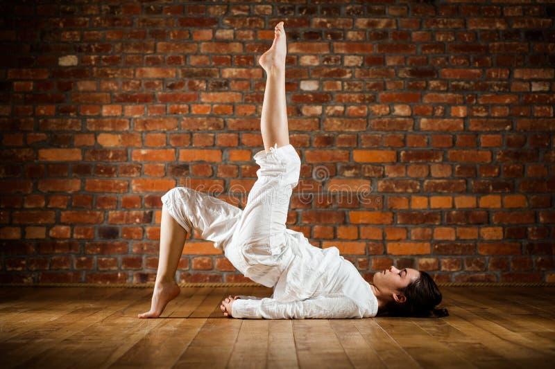 Fille exerçant le yoga contre le mur de briques images stock