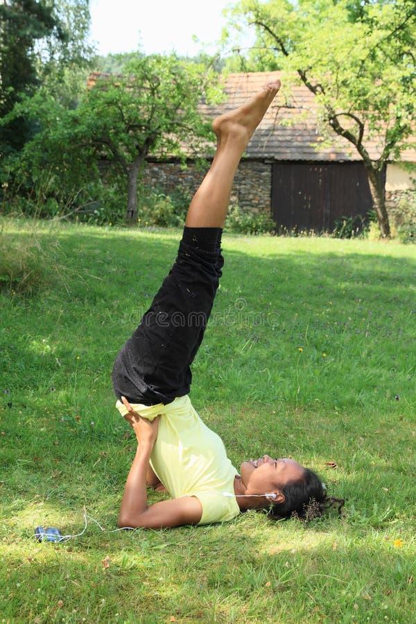Fille exerçant le yoga sur le pré photos stock