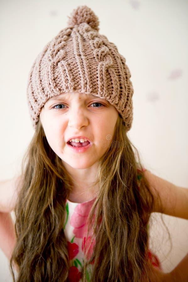 Fille fâchée d'enfant dans le chapeau tricoté beige image libre de droits