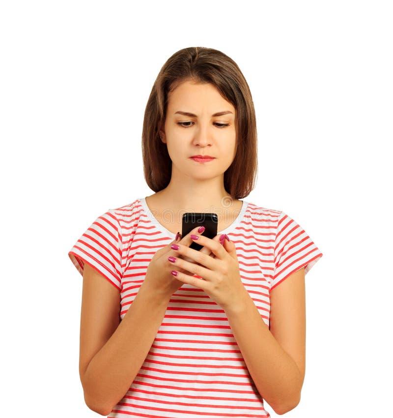 Fille fâchée de portrait jeune regardant le téléphone voyant la mauvaise nouvelle ou les photos avec émotion répugnante sur son v photographie stock libre de droits