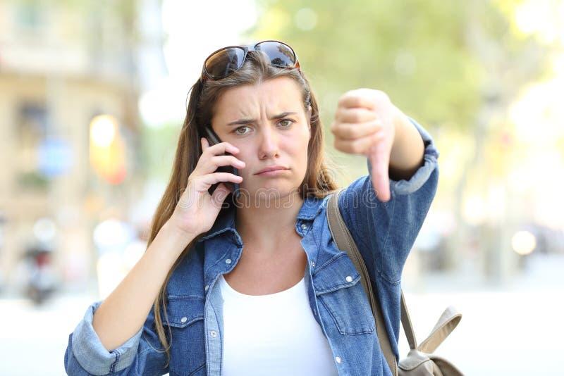 Fille fâchée parlant au téléphone avec des pouces vers le bas images libres de droits