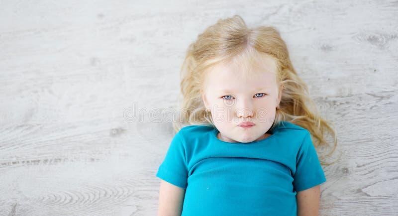 Fille fâchée se trouvant sur le plancher en bois blanc photo stock