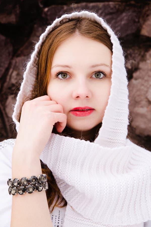Fille féminine dans une écharpe blanche au-dessus d'un mur en pierre images stock