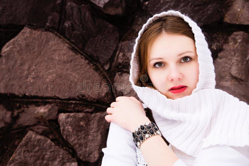 Fille féminine dans une écharpe blanche au-dessus d'un mur en pierre photographie stock libre de droits
