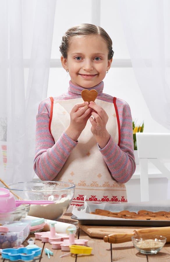 Fille faisant cuire dans la cuisine à la maison, biscuits d'expositions sous forme de coeur, concept sain de nourriture photographie stock