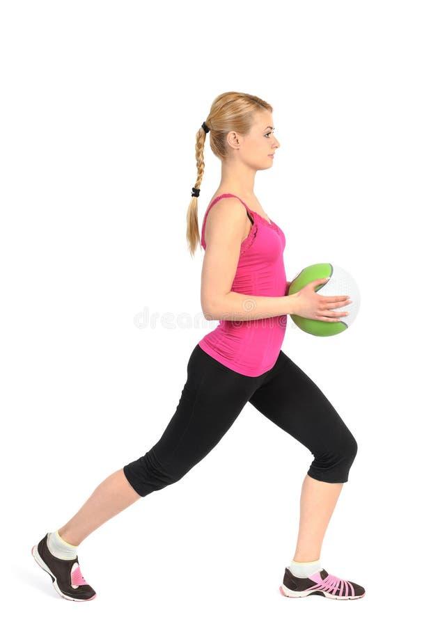 Fille faisant l'exercice de mouvements brusques avec le medicine-ball photos libres de droits