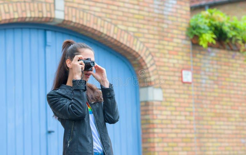 Fille faisant la photo du bâtiment historique avec le rétro appareil-photo sur la rue de ville photographie stock