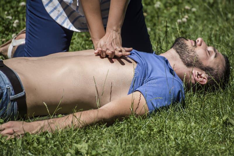 Fille faisant la réanimation cardio-respiratoire à un type inconscient après crise cardiaque image stock