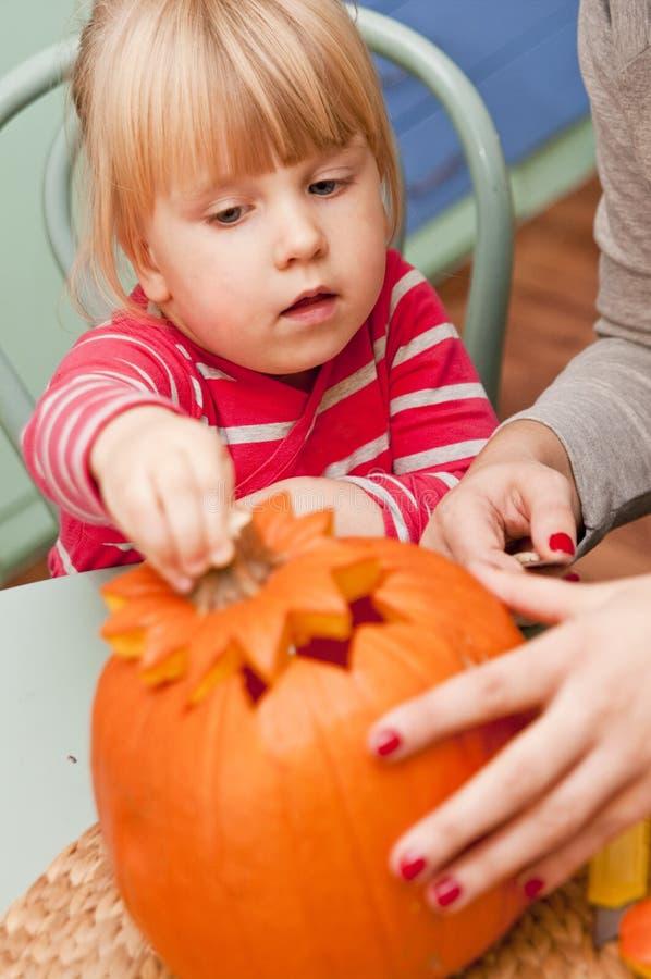 Fille faisant le potiron de Halloween image stock