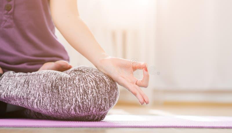 Fille faisant le yoga à l'intérieur dans l'asana de lotus photographie stock