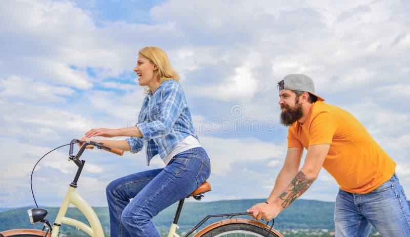 Fille faisant un cycle tandis que l'homme la soutiennent Impulsion de sensation pour commencer à se déplacer La femme monte le fo photo libre de droits