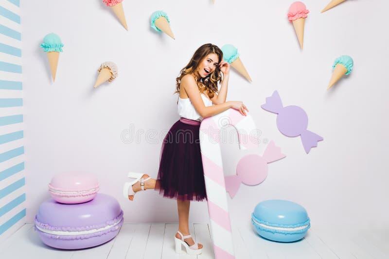 Fille fantastique utilisant la jupe luxuriante foncé-pourpre tenant la canne de sucrerie rose et se tenant sur une jambe avec le  photo stock