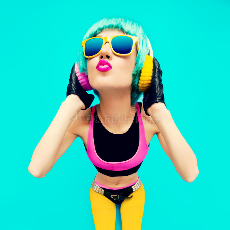 Fille fascinante du DJ de mode dans des vêtements lumineux sur un fond bleu photographie stock libre de droits
