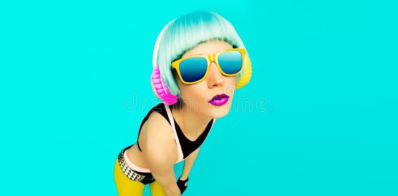 Fille fascinante du DJ de partie dans des vêtements lumineux sur un fond bleu l images stock