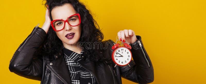 Fille fatiguée de hippie en verres avec le réveil Modèle lumineux étonné sur le fond jaune Horloge d'alarme fatiguée de fixation  photos stock