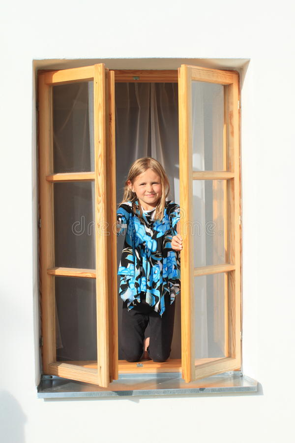 Fille fermant la fenêtre photos libres de droits