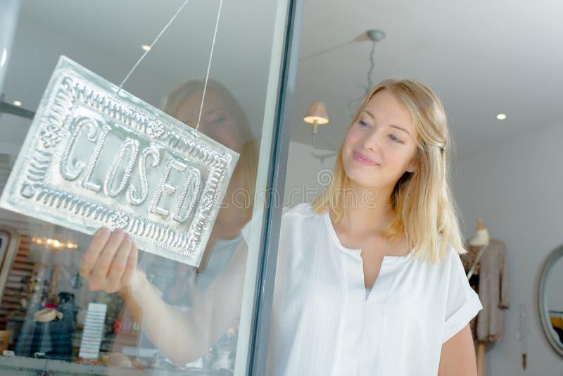 Fille fermant une boutique photo libre de droits