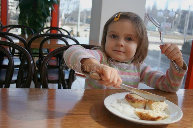 Fille fière à l'aide de la fourchette et du couteau photos stock