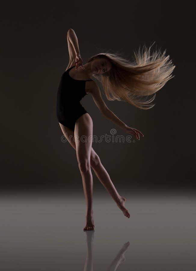Fille flexible avec la longue danse de cheveux blonds Cheveu de vol photographie stock libre de droits