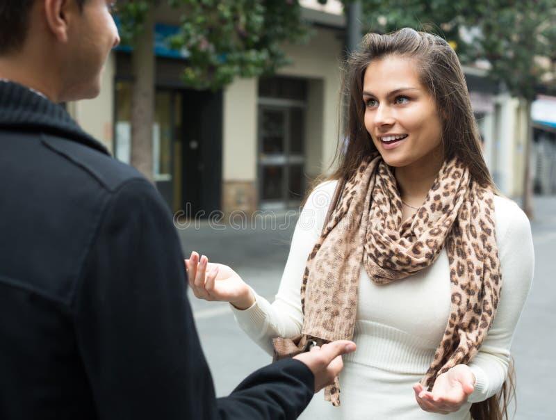 Fille flirtant avec le type à la rue image stock