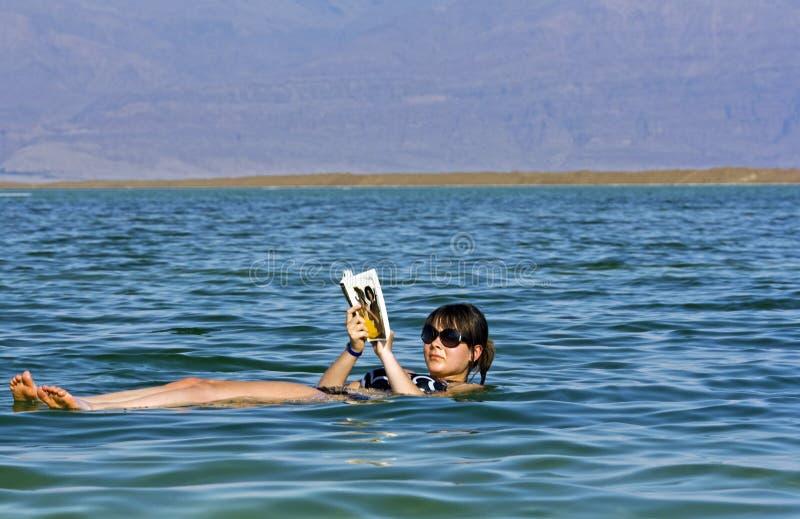 Fille flottant à la mer morte photographie stock libre de droits