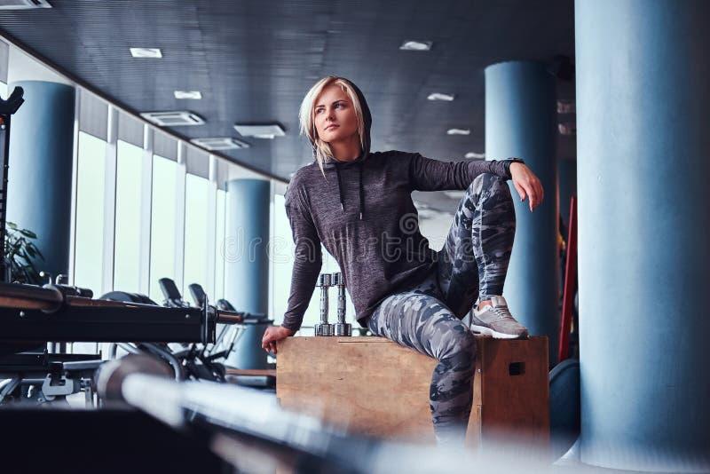 Fille folâtre avec le hoodie de port de cheveux blonds se reposant sur une boîte en bois et regardant en longueur dans le gymnase photos stock