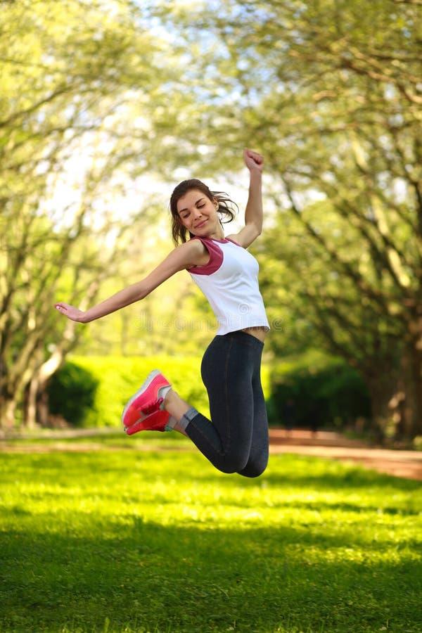 Fille folâtre heureuse sautant en parc vert d'été images libres de droits