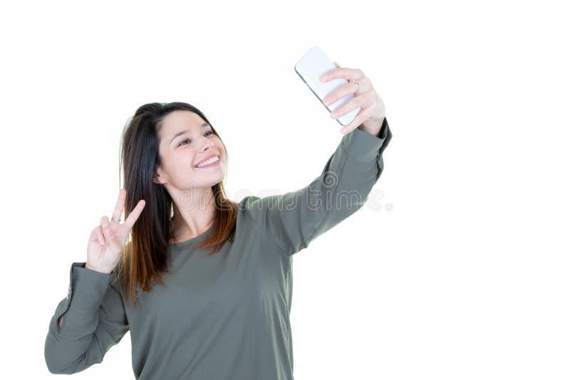Fille fraîche de mode prenant le portrait de selfie d'image sur le smartphone faisant la paix pour signer au-dessus du fond blanc photographie stock libre de droits