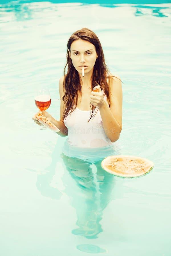 Fille fumant avec la pastèque et le vin dans la piscine images libres de droits