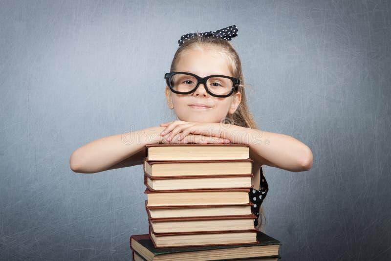 Fille futée avec une pile de livres photographie stock libre de droits