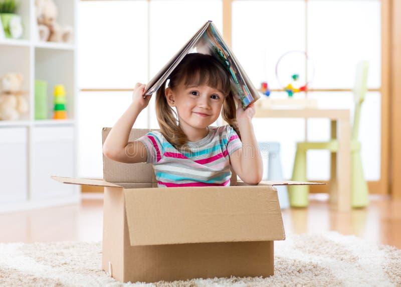 Fille futée d'enfant s'asseyant dans la boîte et tenant un livre au-dessus comme toit image libre de droits