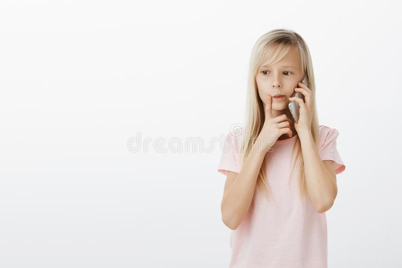 Fille futée focalisée appelle la maman, pensant quoi commande pour le dîner Jeune fille réfléchie concentrée, faisant photo libre de droits
