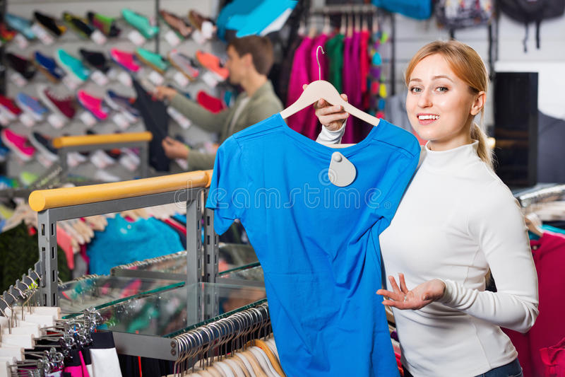 Fille gaie choisissant un T-shirt dans le magasin photographie stock
