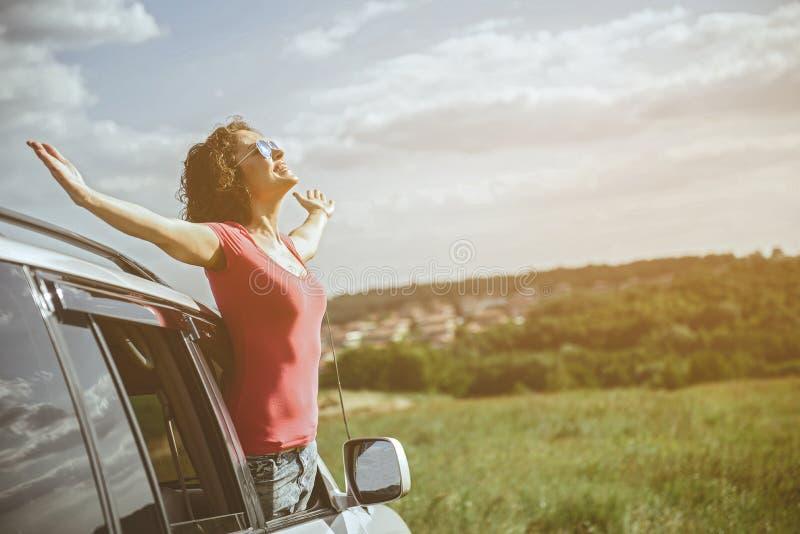 Fille gaie détendant dans l'automobile sur le pré images stock