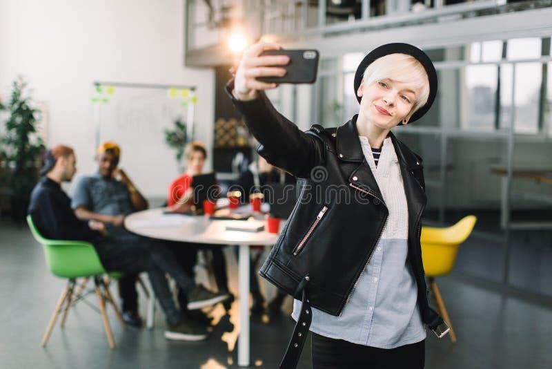Fille gaie dans le chapeau noir et la veste en cuir faisant l'appel visuel par l'intermédiaire du smartphone Main de ondulation d photo libre de droits