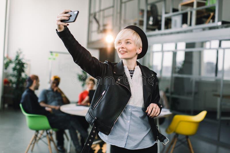 Fille gaie dans le chapeau noir et la veste en cuir faisant l'appel visuel par l'intermédiaire du smartphone Main de ondulation d image libre de droits
