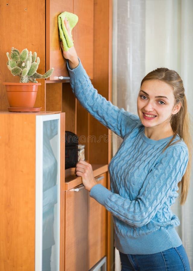 Fille gaie dans le débardeur bleu nettoyant à la maison photos libres de droits