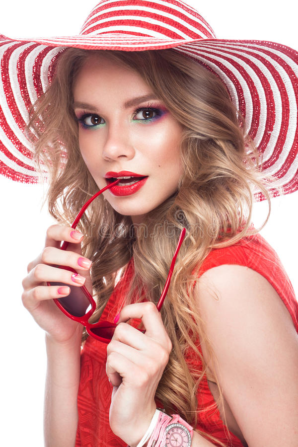 Fille gaie intelligente dans le chapeau d'été, le maquillage coloré, les boucles et la manucure rose Visage de beauté image stock