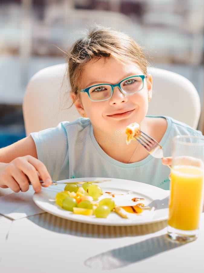 Fille gaie mangeant des crêpes, fruits frais et buvant du jus d'orange pendant le mode de vie sain de petit déjeuner, le régime v photos stock