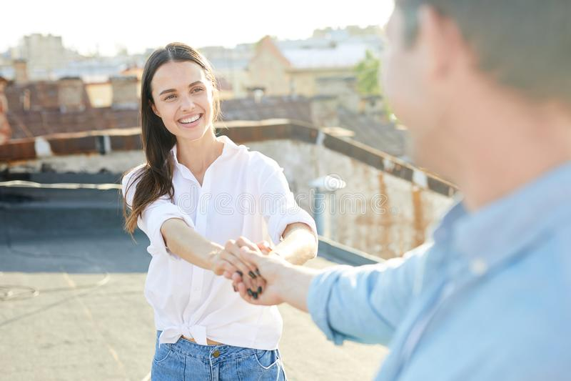 Fille gaie marchant avec l'ami sur le toit photographie stock